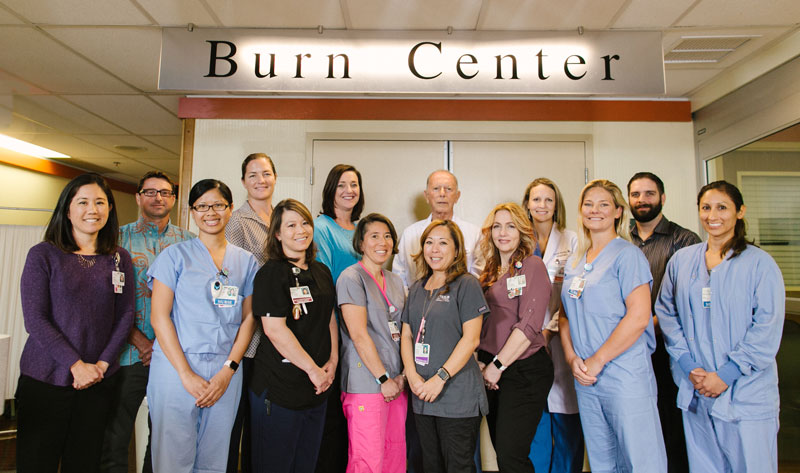 physicians and staff of the Straub Burn Center stand in front of the office doors and sign