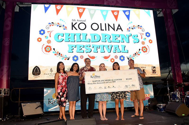 Group on stage at Ko Olina Children's Festival holding ceremonial check for $65,000