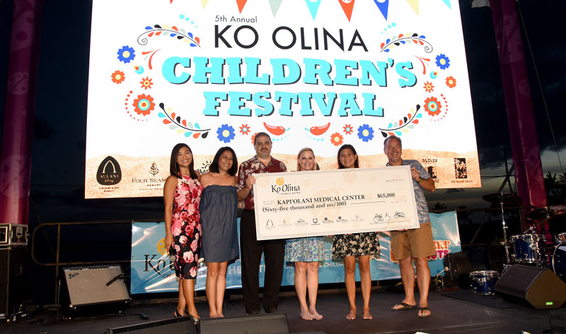 A group of people stand on stage hold a check during a presentation at the Ko Olina Children's Festival.