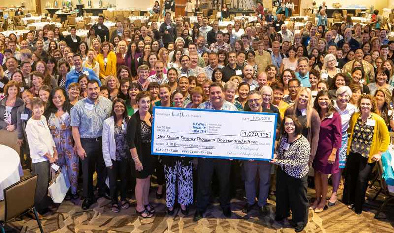Hawaii Pacific Health employees gather with President & CEO Ray Vara (center behind check) to celebrate the results of the 2018 Hawaii Pacific Health Employee Giving Campaign, which raised more than $1 million for the second year in a row