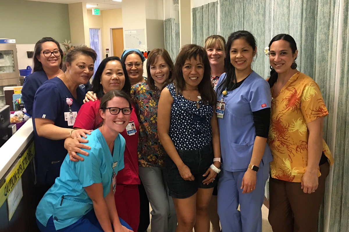 Cheri Beddow poses for a group photo with nurses in the Pali Momi Infusion Center