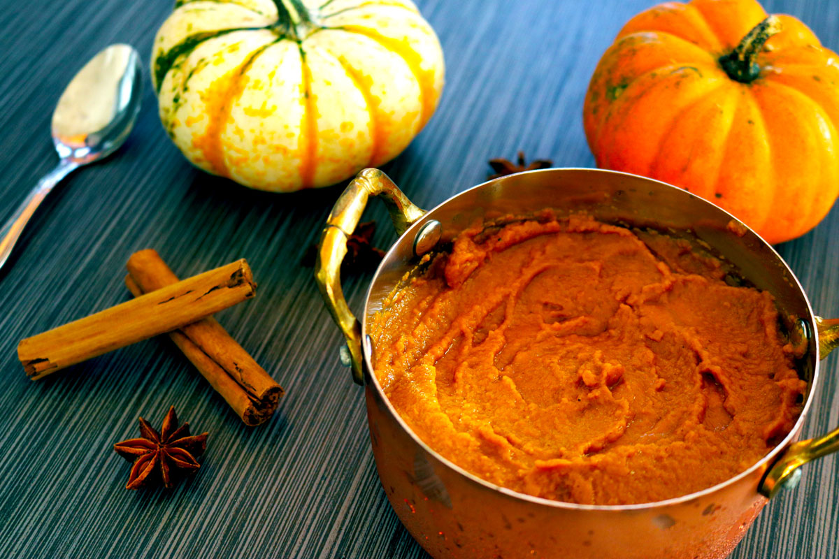 a bowl of Pumpkin Pudding sits on a table decorated with pumpkins, cinnamon sticks and star anise seeds