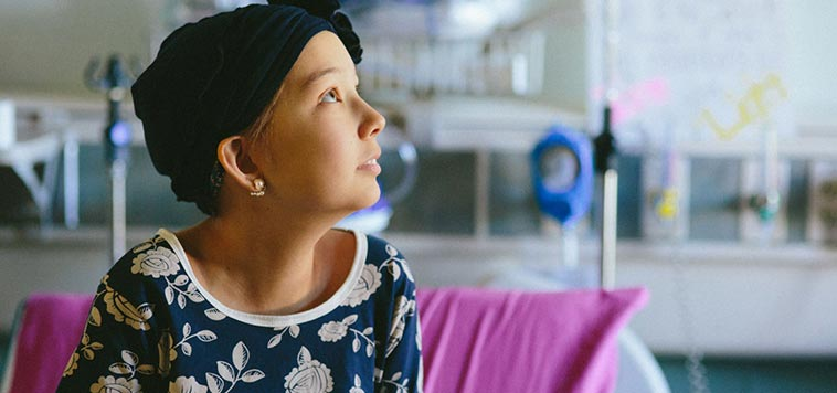 young child with cancer looks up hopefully from hospital bed