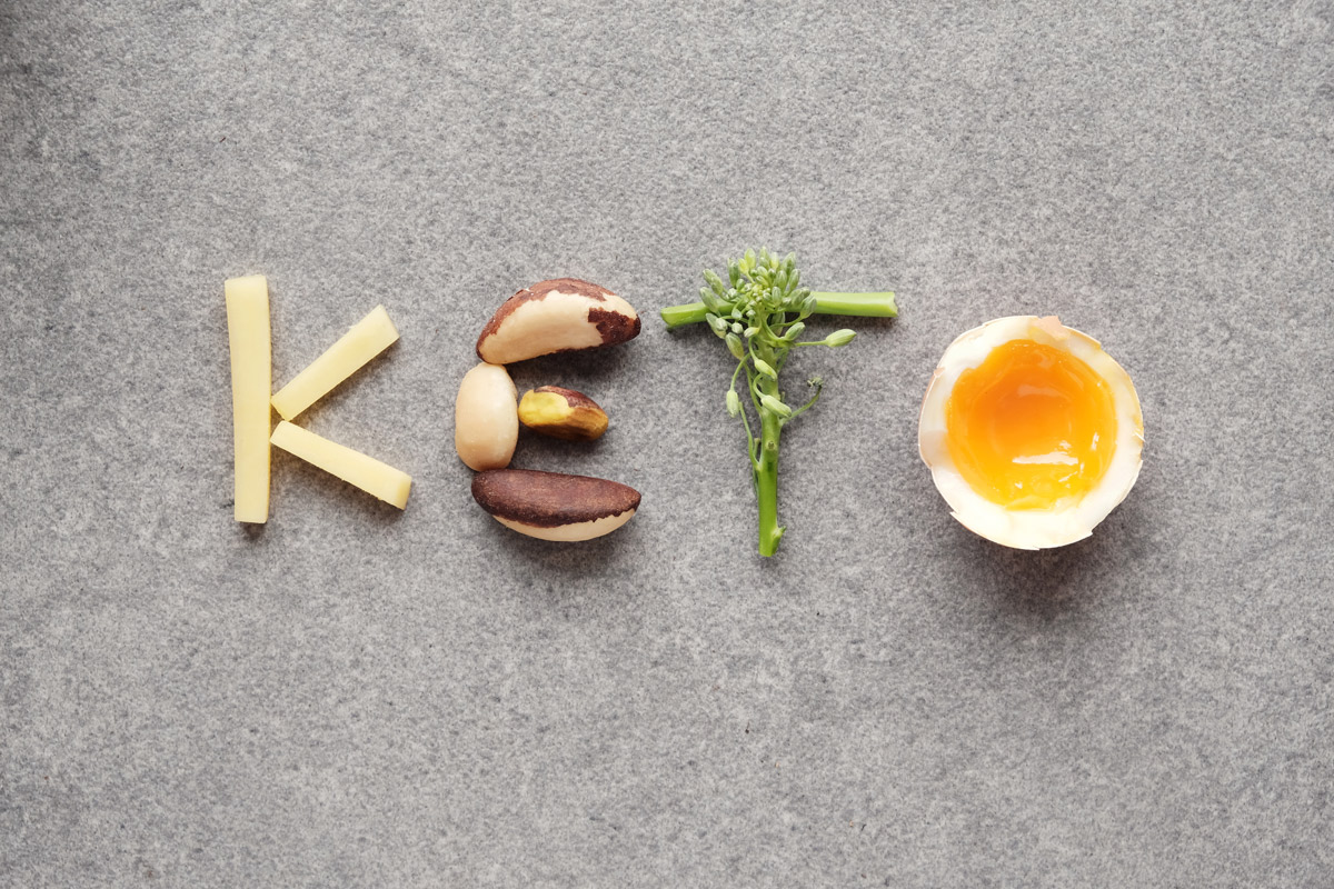"cheese, nuts, broccoli and a soft-boiled egg spell out the word ""KETO"""