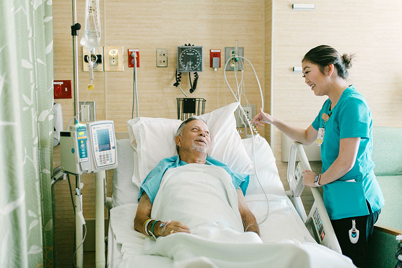 Nurse standing beside patient in hospital bed