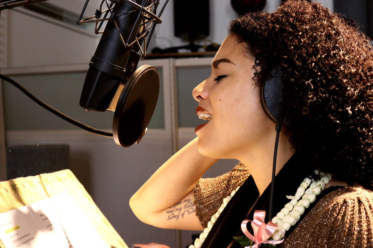Jenene Ahia singing into a microphone in a recording studio