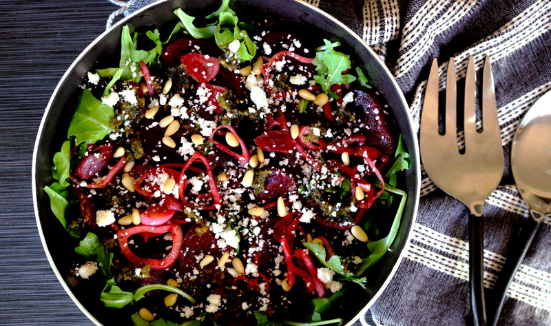 a bowl of Roasted Beet Salad with Basil-Lemon Pesto sits on a dark counter top next to a napkin and serving utensils