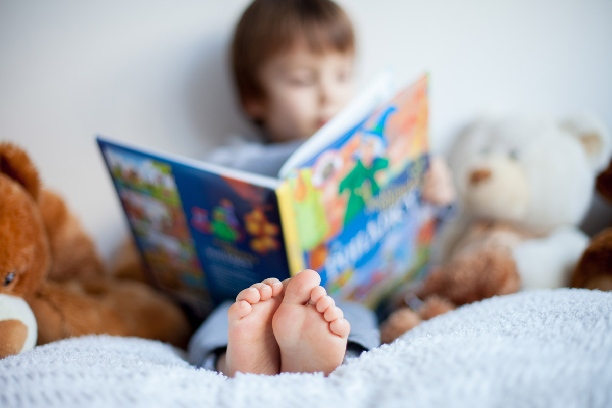 young boy reads a book in bed surrounded by stuffed animals