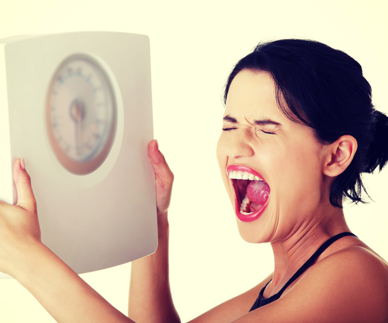 young woman holding up scale and screaming in frustration