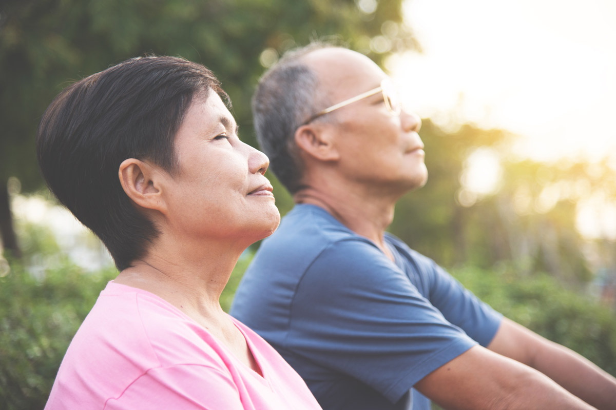 an elderly couple practices meditative breathing exercises in an outdoor park