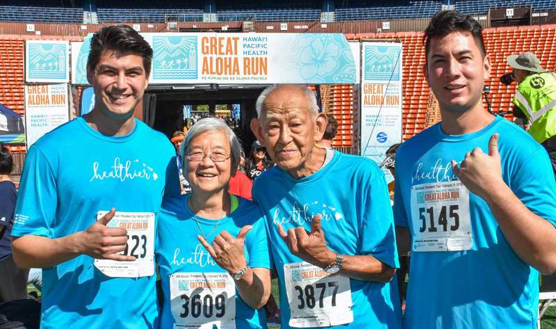 man, daughter and two grown grandsons wave a shaka at the finish line of the Great Aloha Run