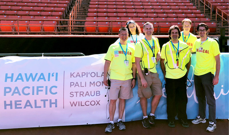 Medical volunteers stand in front of a Hawaii Pacific Health banner at the Great Aloha Run finish at Aloha Stadium