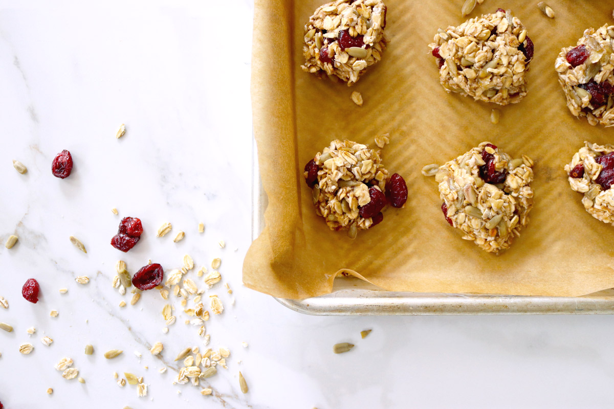 4-Ingredient Breakfast Cookies on a parchment-lined baking sheet sit on a marble counter top sprinkled with oats, sunflower seed kernels and dried cranberries