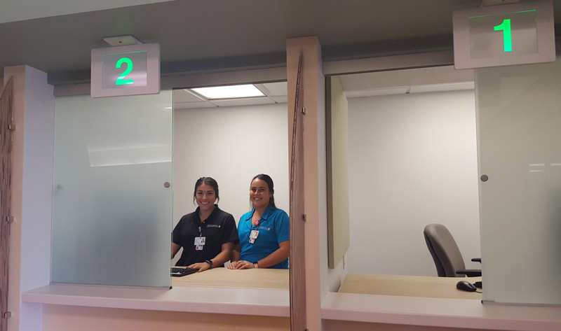 Two medical assistants stand behind the glass windows of the central registration check-in system