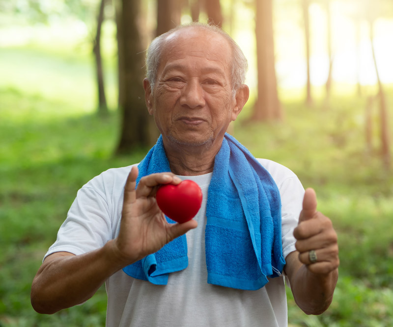 elderly man with a sports towel draped over his shoulders standing outside in a wooded area holding a small felt heart