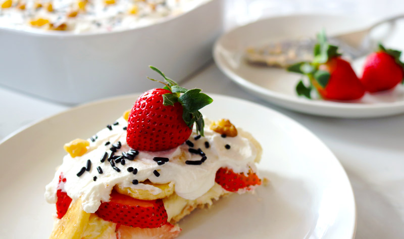 two slices of No-Bake Banana Split Cheesecake topped with fresh strawberries and chocolate sprinkles presented on clean white plates next to a large ceramic baking dish of cheesecake with a large portion sliced out