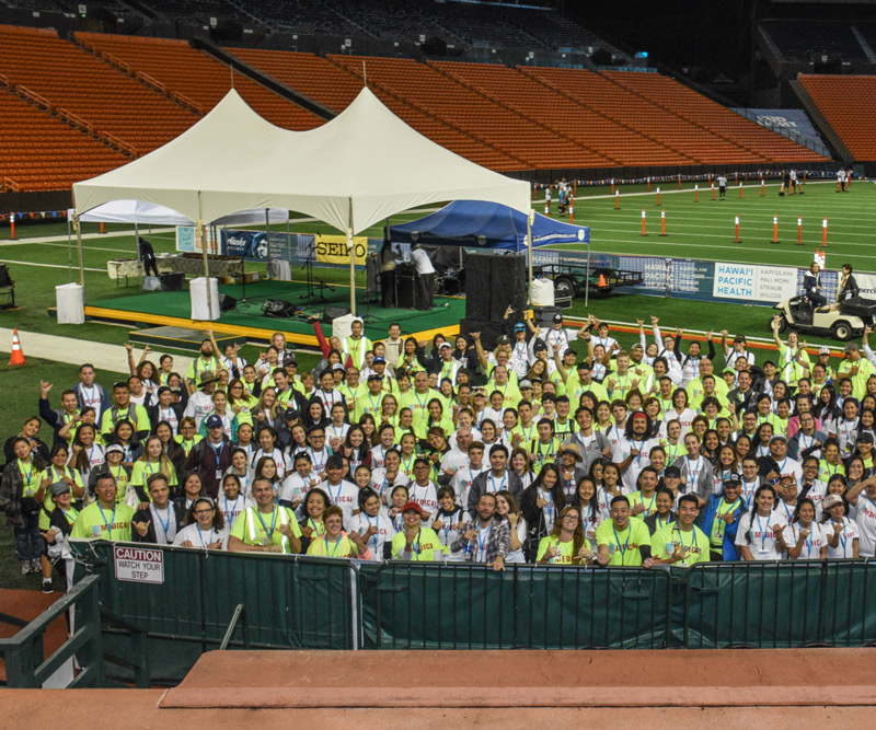 Volunteers gather on the field of Aloha Stadium for a safety brief before the start of the Great Aloha Run
