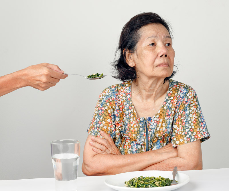 elderly woman with arms crossed refusing to eat a spoonful of food presented to her by a loved one