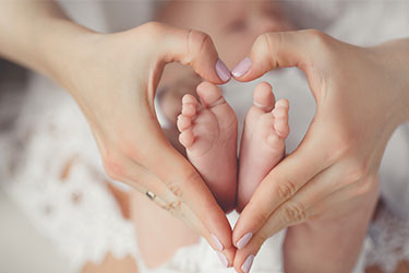 mother forming an heart with her hands around babies feet