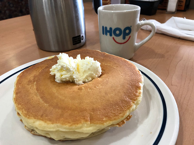 Plate of pancakes and a cup of coffee with IHOP logo