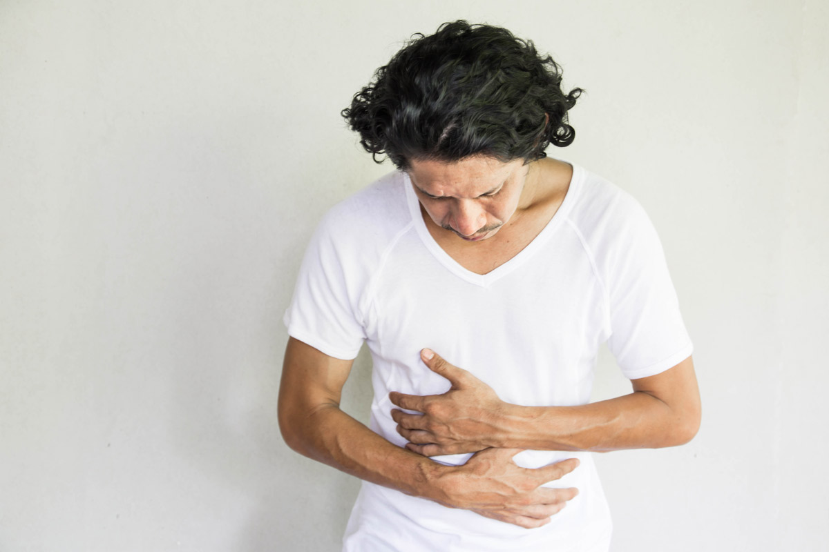 middle-aged man in a white T-shirt holds his stomach with a look of pain on his face to indicate possible colon cancer