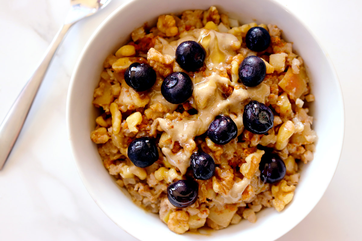 a bowl of Cauli-Oats topped with blueberries sits on a marble counter top with a spoon resting in the background