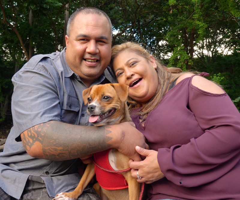 Charlyn Esera and fiance Chad sit together hugging with their small brown dog, Honey Girl, between them