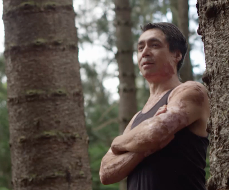 Lance Kaanoi stands in a forest of trees with his arms crossed, looking with determination off into the distance