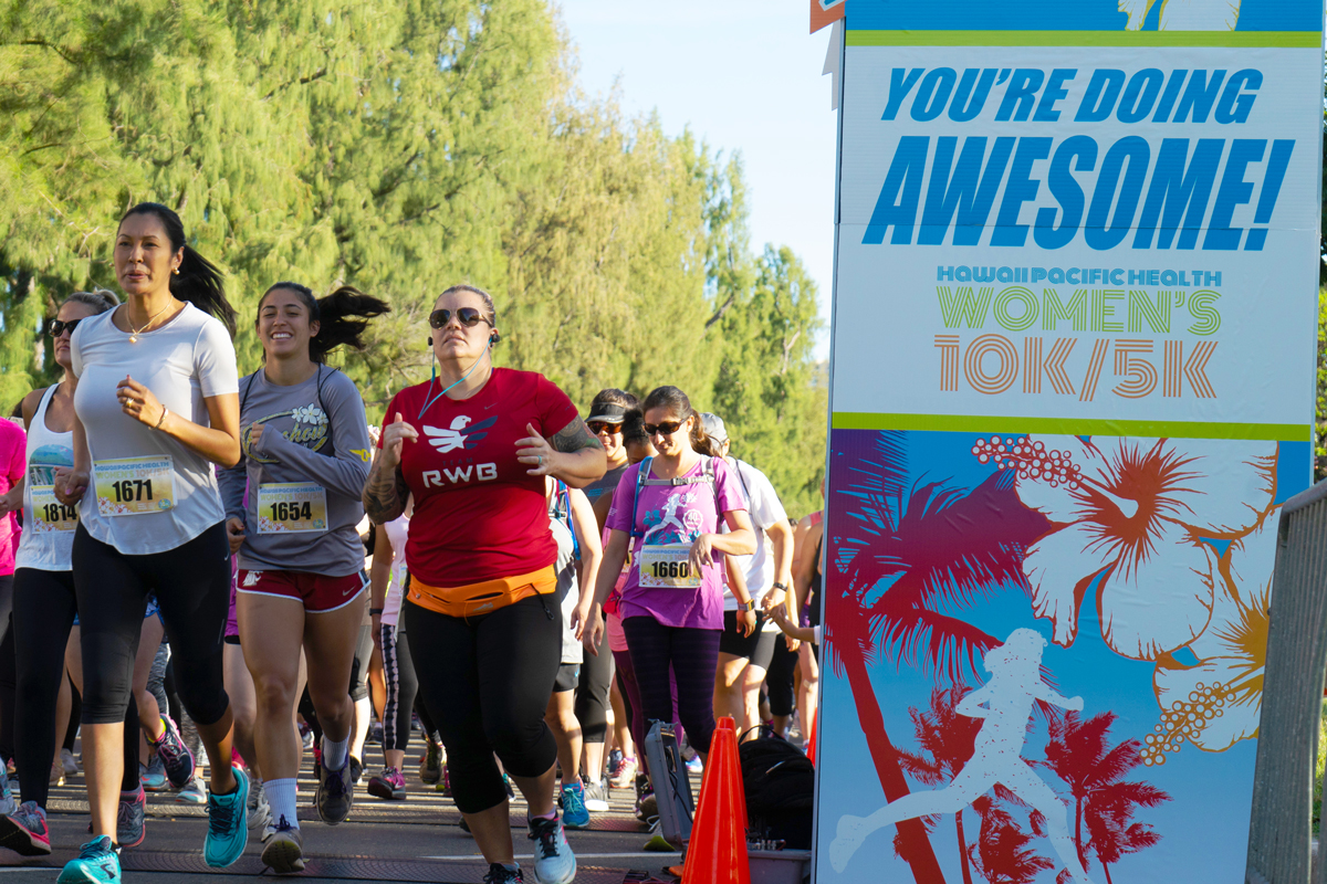 "Women cross the starting line of the 2018 Hawaii Pacific Health Women's 10K with the encouraging words of ""You're Doing Awesome"" printing on the starting arch."
