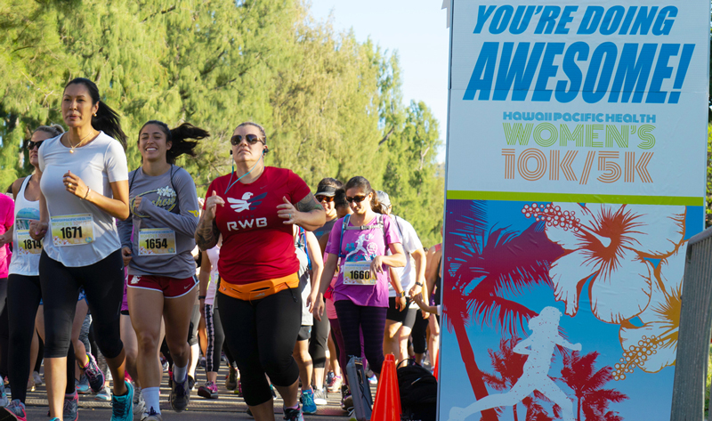 "Women cross the starting line of the 2018 Hawaii Pacific Health Women's 10K with the encouraging words of ""You're Doing Awesome"" printing on the starting arch"