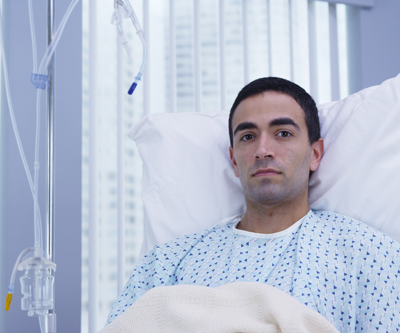 A young man in a hospital bed intensely stares directly into the camera