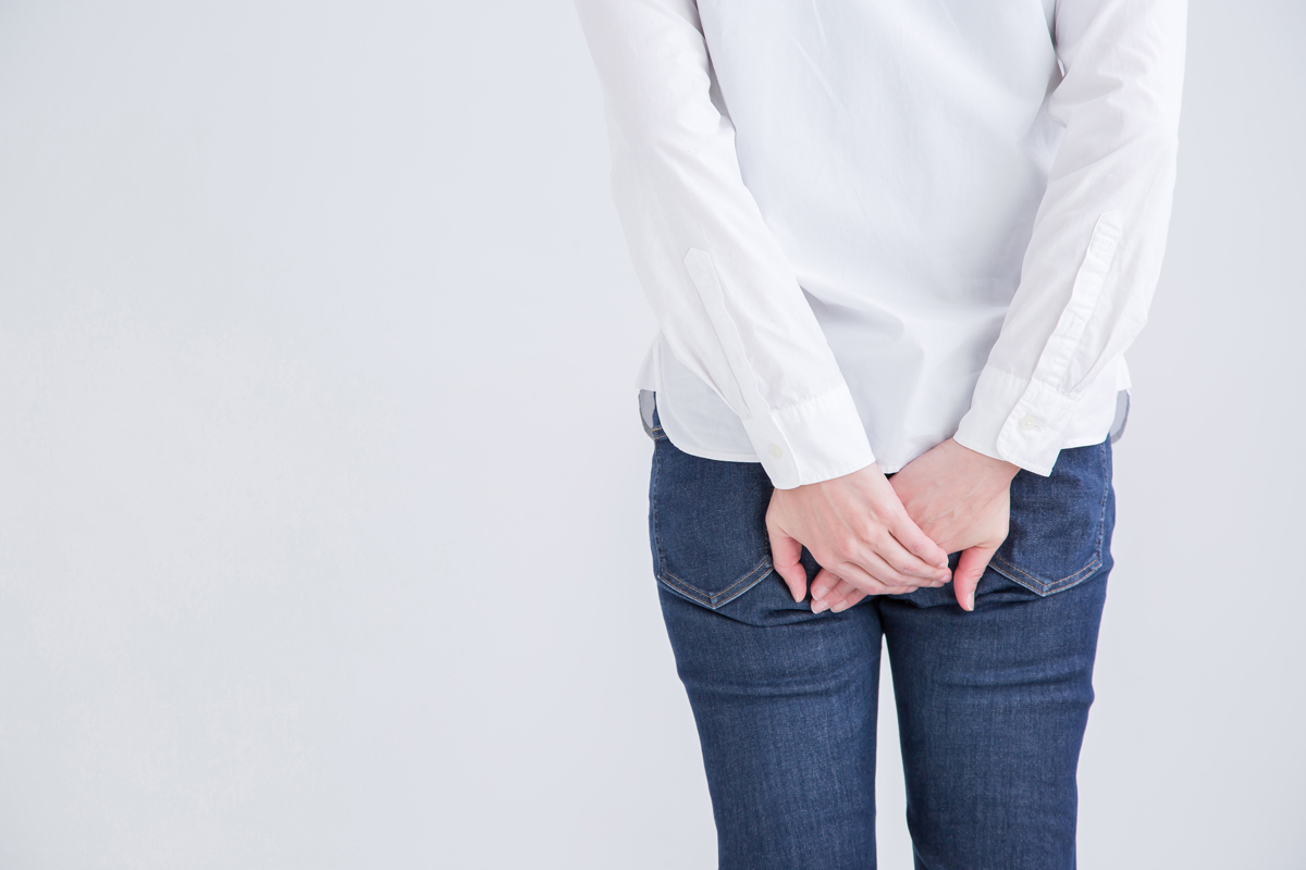 a woman dressed in a white blouse and jeans places her hands over her butt