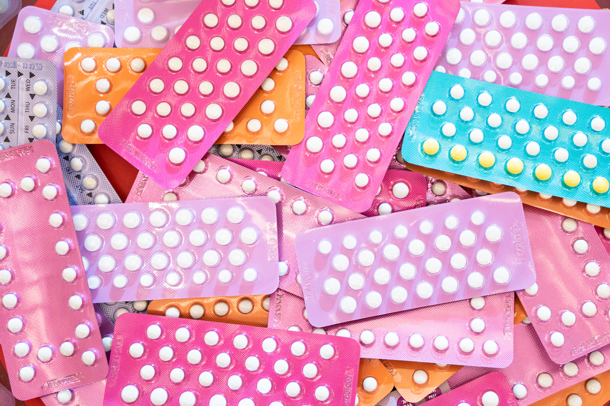 brightly colored packs of The Pill birth control method piled on top of each other