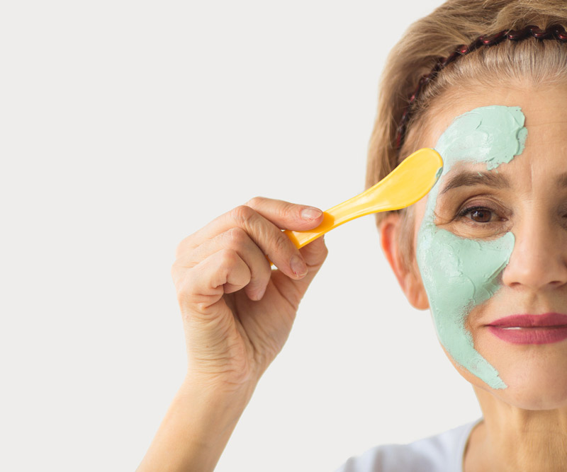 an older woman applies a green face mask to her skin