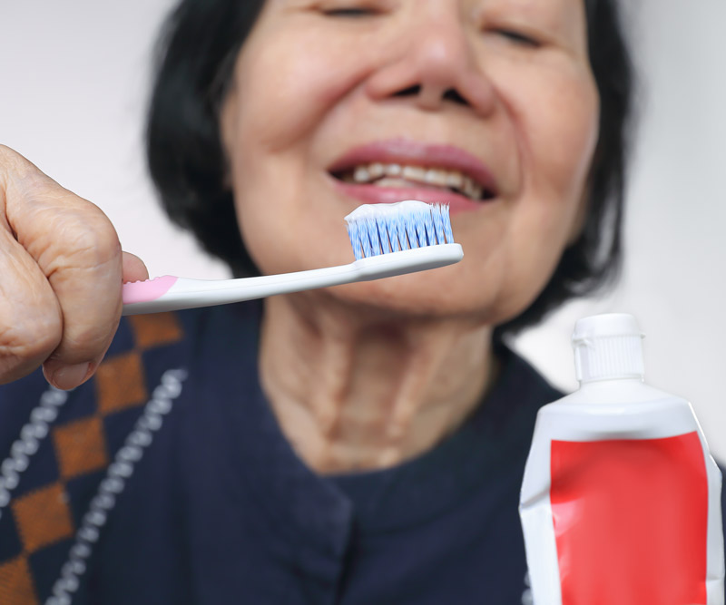 close-up of an elderly Asian woman squeezing toothpaste onto a toothbrush