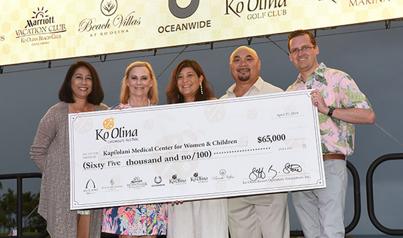 Three women and two men on stage holding ceremonial check for $65,000