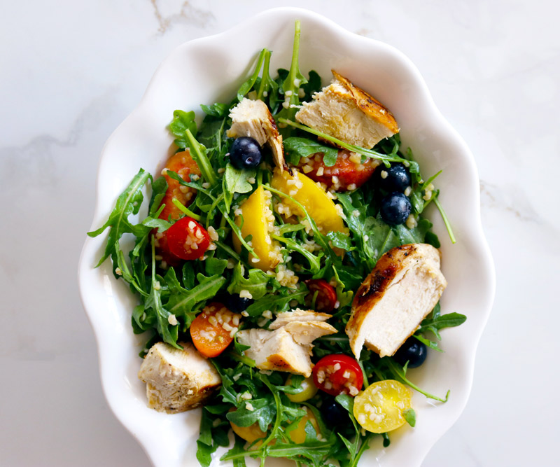 a white bowl filled with Chicken & Bulgur Salad made with arugula, grilled chicken, bulgur, cherry tomatoes, peaches and blueberries sits on a white marble counter top