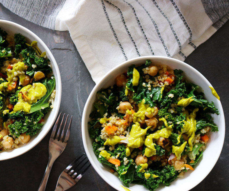 two Kale & Chickpea Harvest Bowls drizzled with bright-green Avocado Dressing arranged on a slate counter top next to two forks and a beige-and-black dish towel