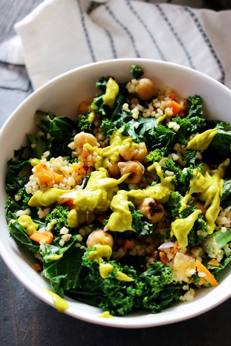 Protein-rich chickpeas combined with fiber-full carrots, kale and bulgur get topped with a generous drizzle of a thick homemade avocado dressing for a well-rounded one-bowl meal.