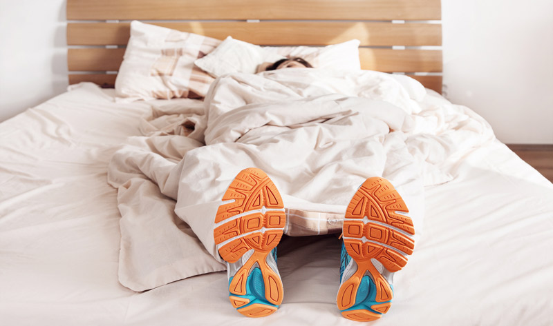 orange-soled athletic shoes stick out from under the covers of a comforter on a bed