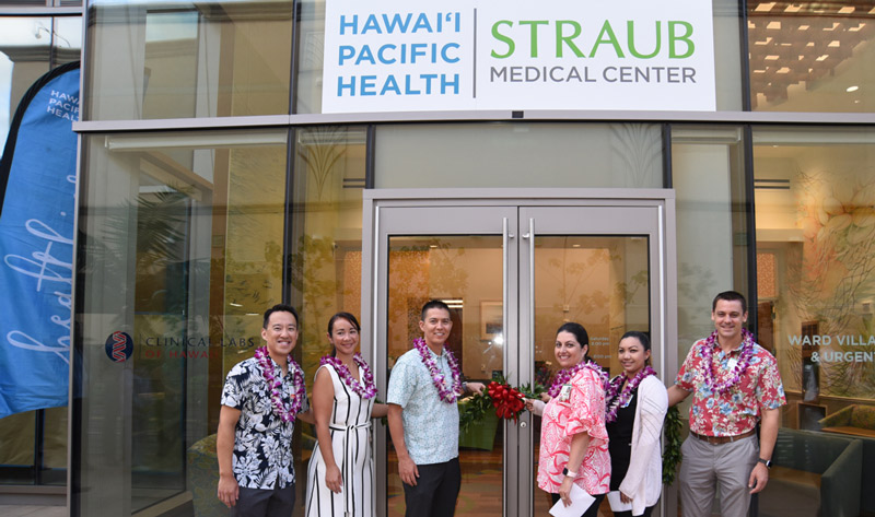 Three men and three women get ready to untie a maile lei draped in front of the glass doors of the new Straub Ward Village clinic
