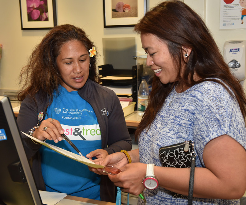 Aida Corpuz (right) reviews paperwork prior to receiving free cervical cancer and breast cancer screenings at the Kapiolani Women's Center as part of an event put on through a grant from College of American Pathologists (CAP) Foundation's See, Test & Treat program.