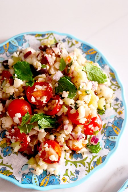 Tomatoes, cucumber, onions, cauliflower and olives mix beautifully with fresh herbs and a citrusy vinaigrette to create an edible garden on a plate.
