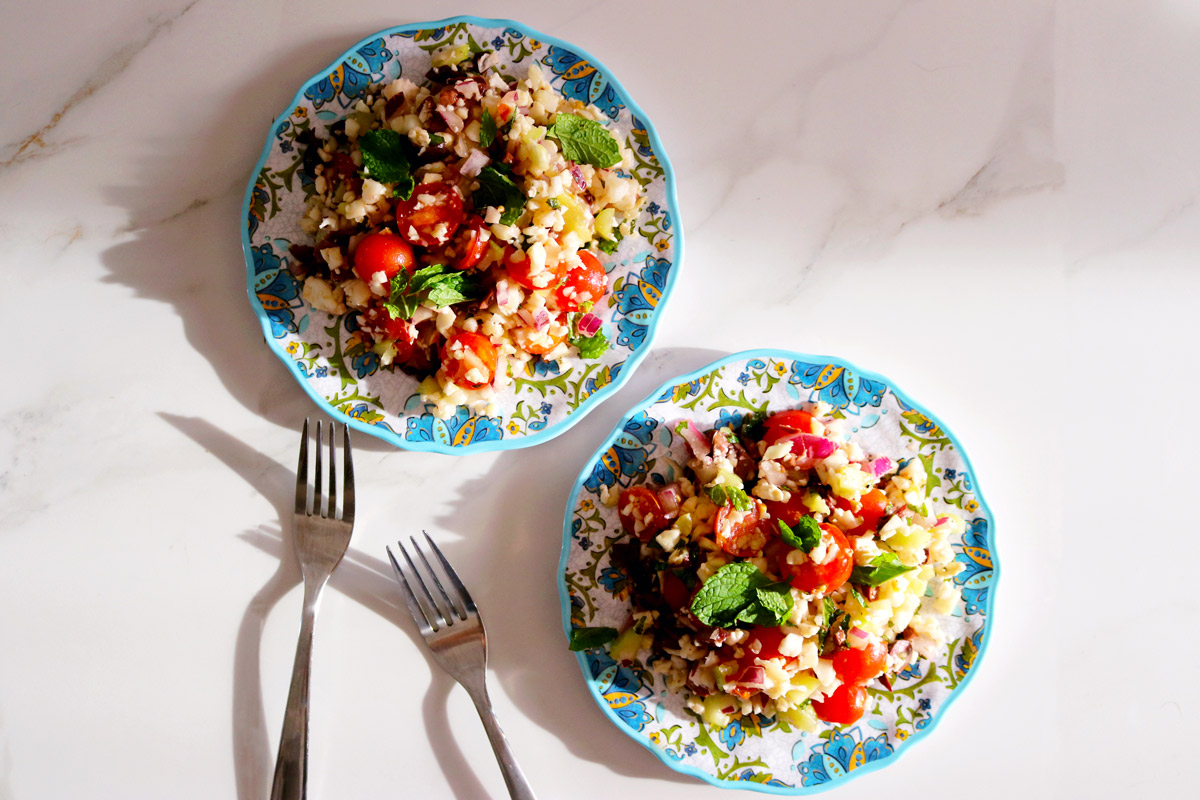 two colorful plates of Summer Tabbouleh on a marble counter top next to two forks