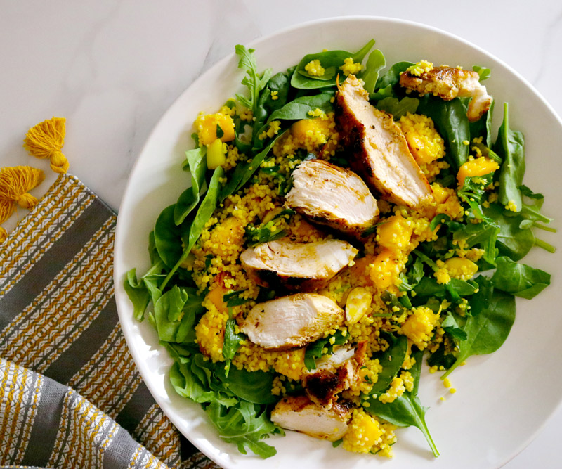 a plate of Curried Chicken Mango Couscous Salad on a marble counter top