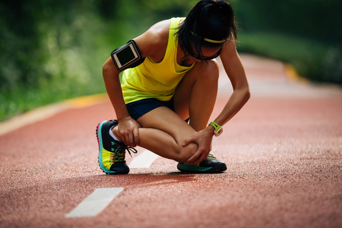 athletic woman bent over holding shin in pain while on a run outdoors