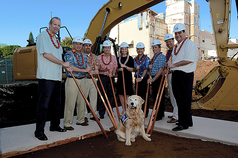 a group of people with hard hats and shovels with a dog and a large digger in the background