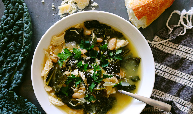 a bowl of Slow Cooker Chicken Stew surrounded by kale leaves, crumbled Parmesan cheese and a torn baguette