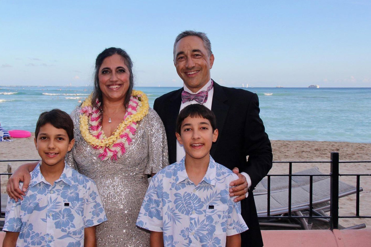 a man and woman with their two young boys stand on the balcony of a beachfront hotel in Hawaii