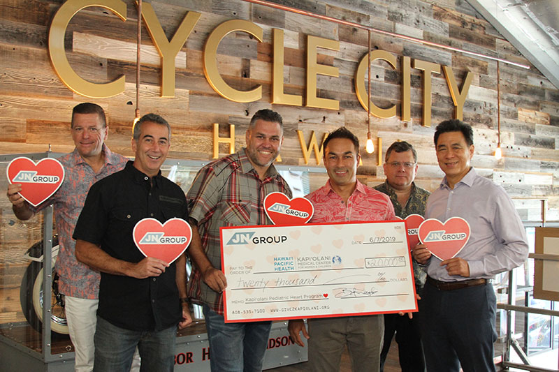 Group of men holding red hearts and a ceremonial check to Kapiolani for $20,000